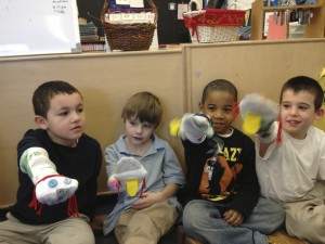 Children play with handmade sock puppets in a Boston classroom.
